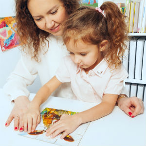 Young girl putting together a puzzle with her mother