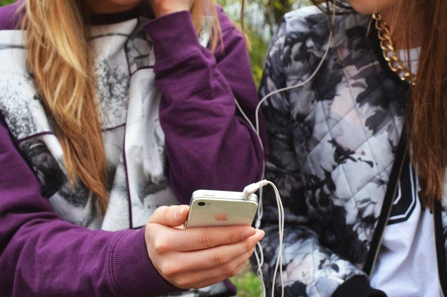Two teenage girls listening to music on a smartphone