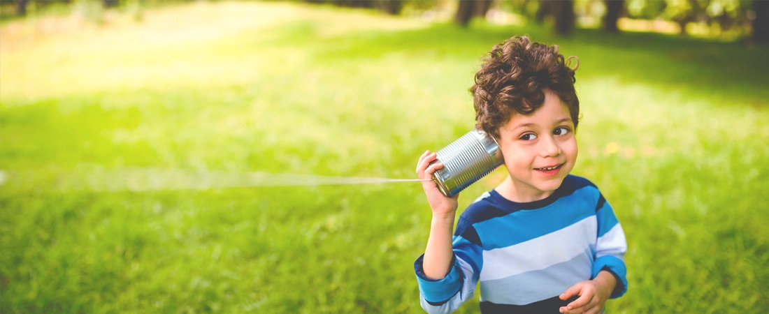 Child listening to his friend through a tin can and string