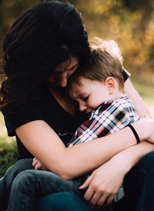 mother holding crying child